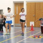 High Schoolers, Lizzie Illiev and Kiarah Horn assisting 1st graders at the Beanbag Dribble Relay